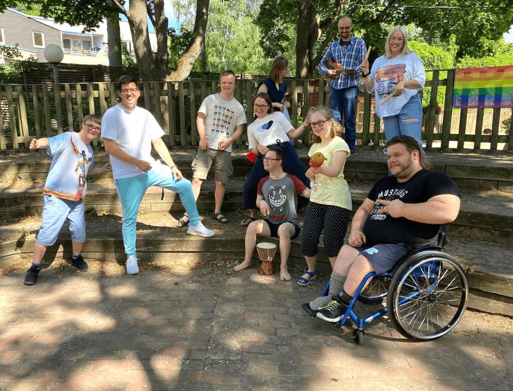 Eine Gruppe Jugendlicher mit Down-Syndrom, die fröhlich für das Bild posieren. Mit dabei sind 3 Erzieher und eine Erzieherin. Einer der Erzieher sitzt im Rollstuhl.